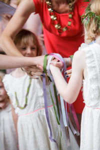 A celebrant leads a handfasting ceremony and is seen tying coloured ribbons around four-linked hands.