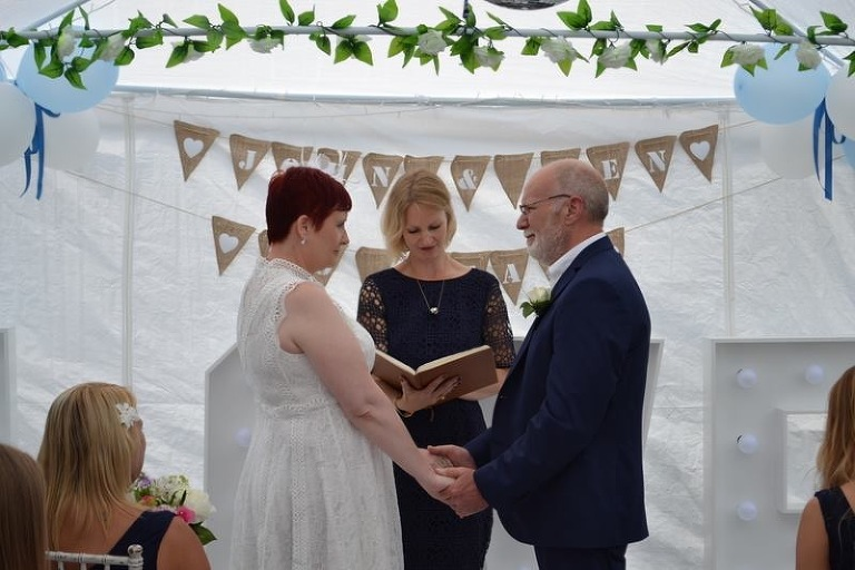 A celebrant helps a couple exchange new marriage vows in a renewal of vows ceremony