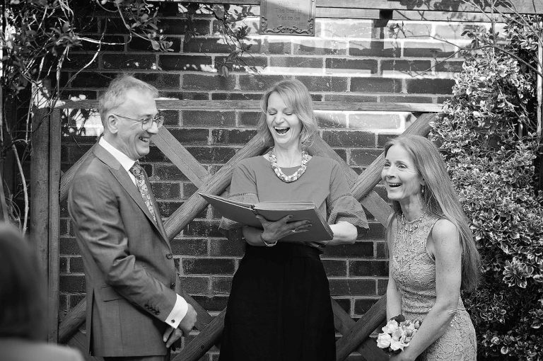 Man and woman renewing their wedding vows with a celebrant-led ceremony, all laughing