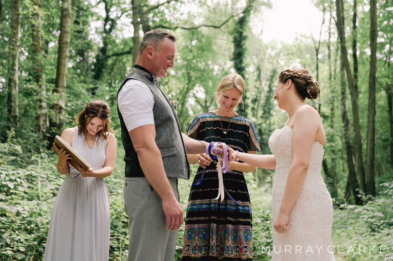 A bride and groom stand in a woodland glade on their wedding day. A wedding celebrant is binding their hands with ribbons as part of a traditional handfasting ceremony. They are all laughing and smiling.