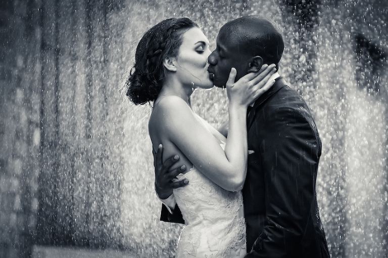 Professional photo of a wedding couple kissing in the rain.