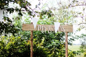 Mr & Mrs' wedding sign with bunting set against the backdrop of trees