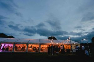 Lare stretch tent decorated for a wedding lit up with fairy lights against a dark sky