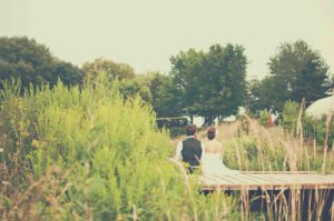 Bride and Groom sitting on wooden jetty overlooking a lake, with back to camera