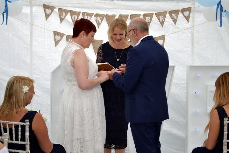 A celebrant helps a husband and wife couple renew their vows for their wedding anniversary