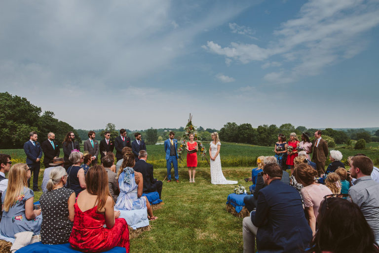 A bride and groom stand beneath a flower arch in an outdoor wedding ceremony; being led by a wedding celebrant