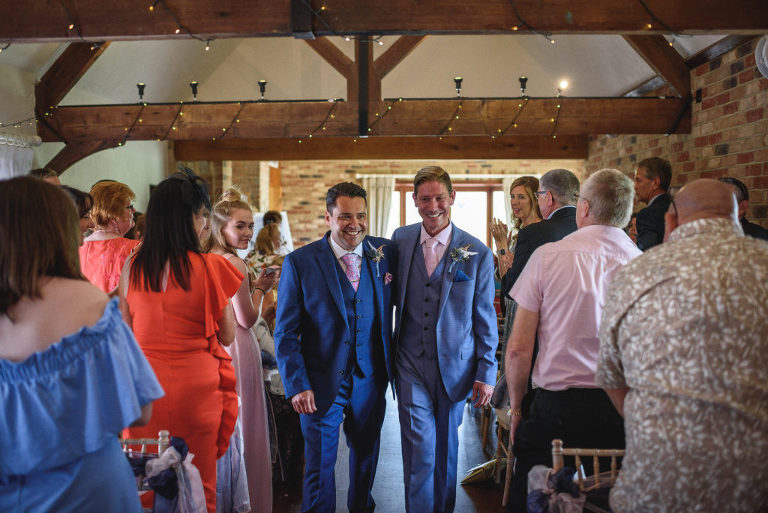 Two smiling men in blue suits walk back down the aisle to cheers and applause from their wedding guests