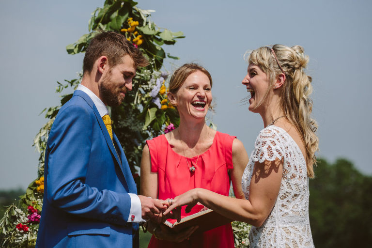 A bride and groom stand facing one another laughing and smiling as they take they exchange rings. The ceremony is officiated by a wedding celebrant.