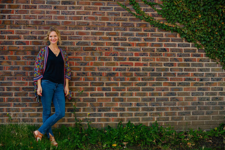Woman in causal pose stands leaning against a brick wall