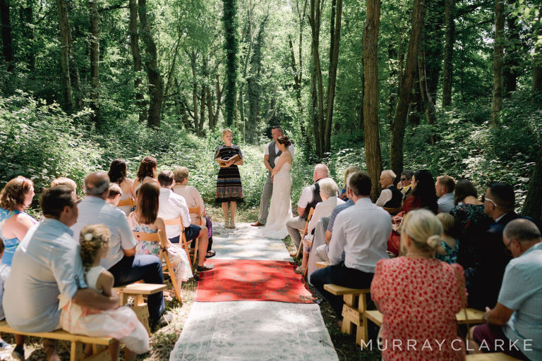Shows a woodland wedding and a couple taking their vows with a Celebrant leading the ceremony